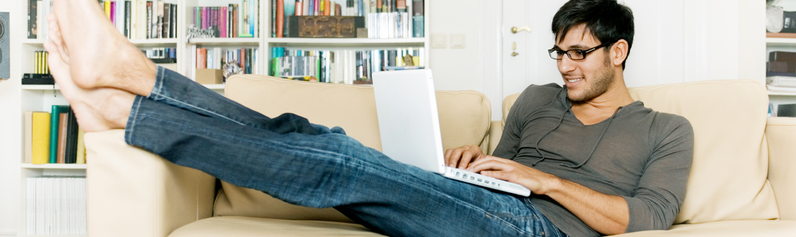 Person on couch checking laptop