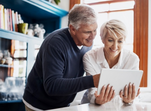 couple using tablet device in kitchen