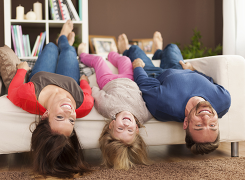 Family hanging upside down on couch